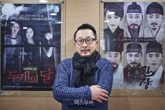 주피터필름의 제작 영화인 <두 개의 달>과 <관상> 포스터 앞에서 포즈를 취한 주필호 대표. ⓒ맥스무비 김미애 (에이전시 테오)